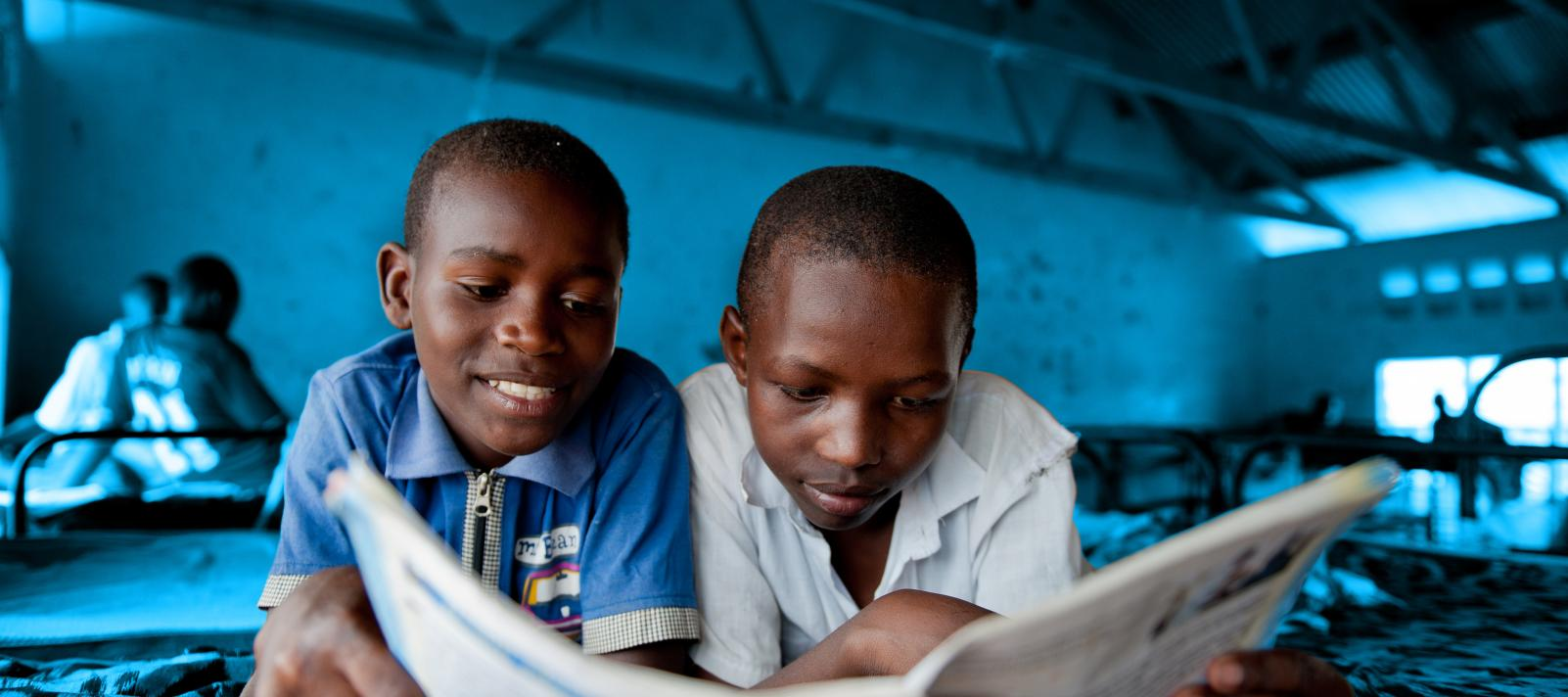 Two boys reading a book in their school dormitory.