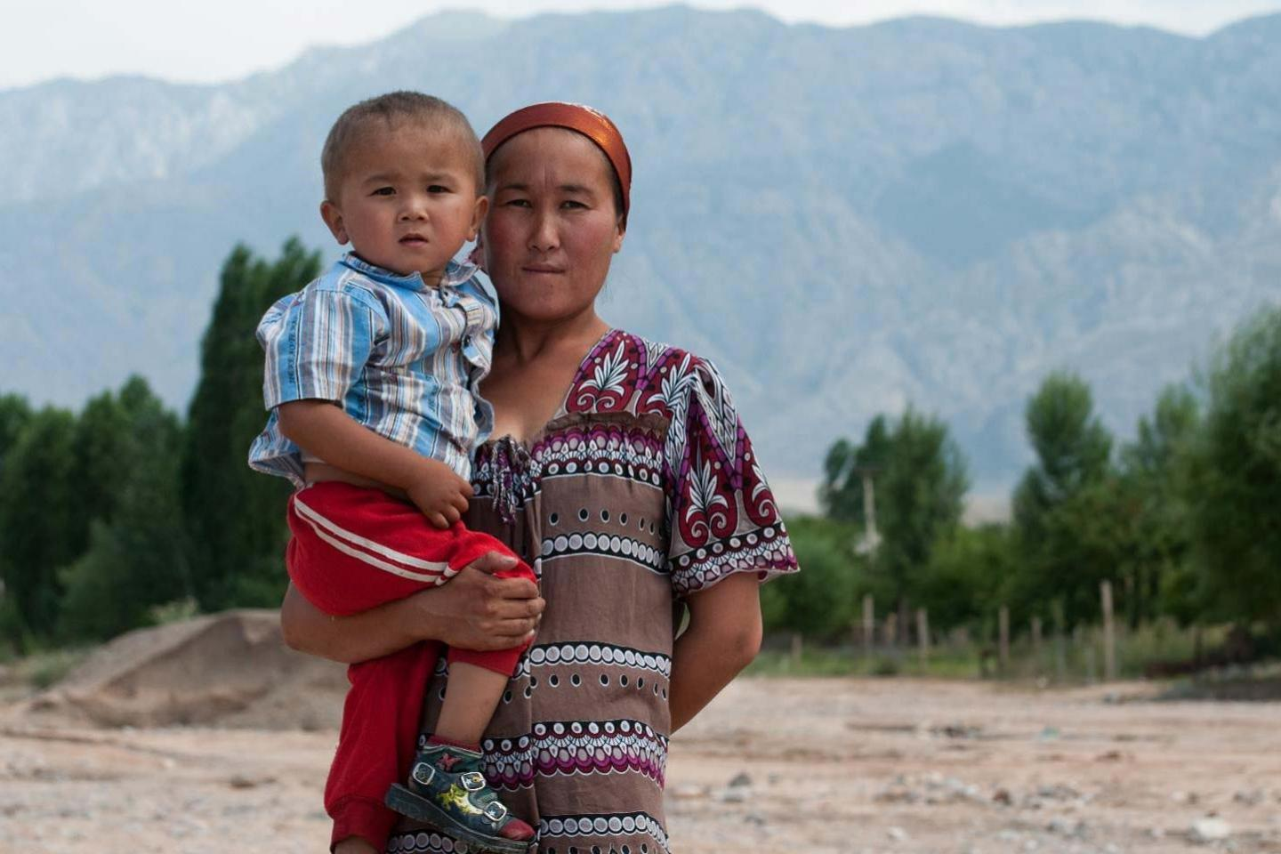A mother holds her son in her arms against a mountainous backdrop