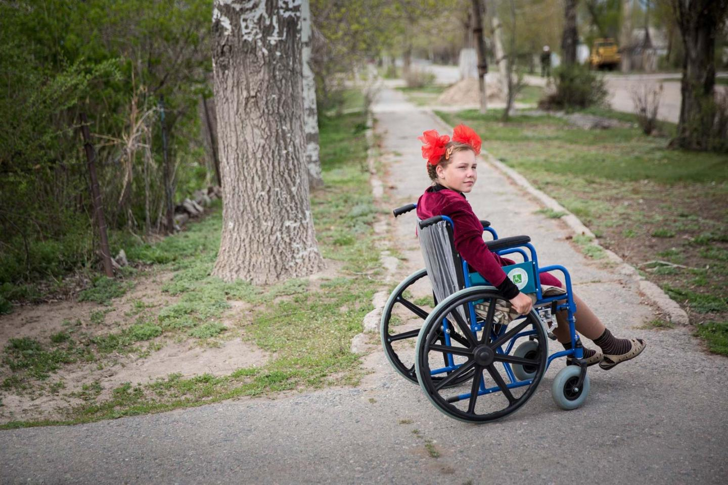 A girl in a wheelchair on a tree-lined sidewalk