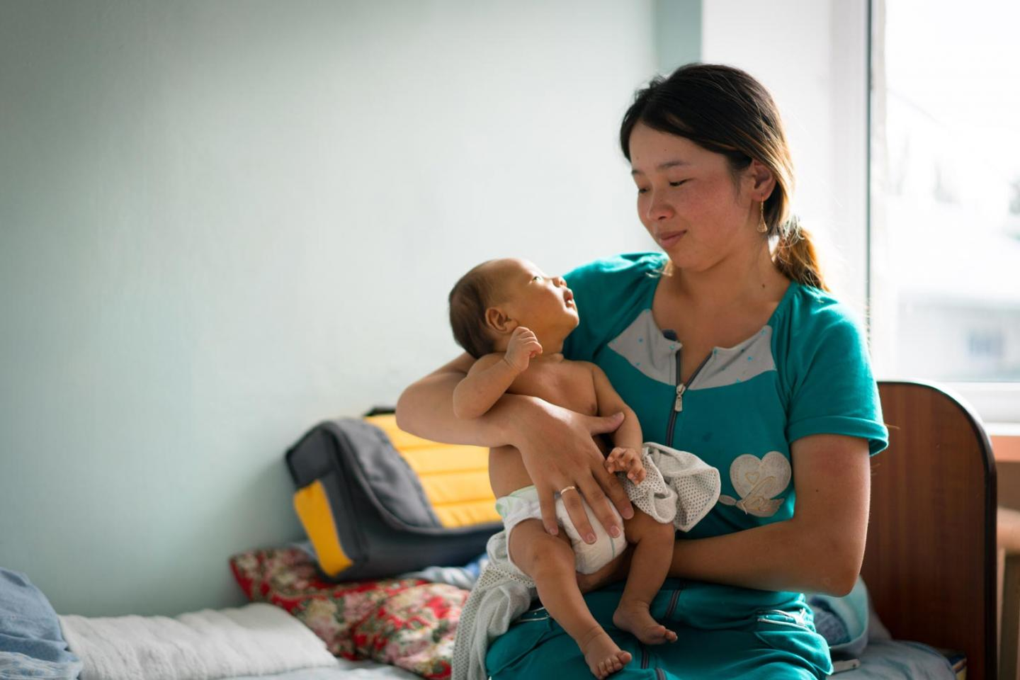 A young mother in turquoise dress holds an infant in her arms