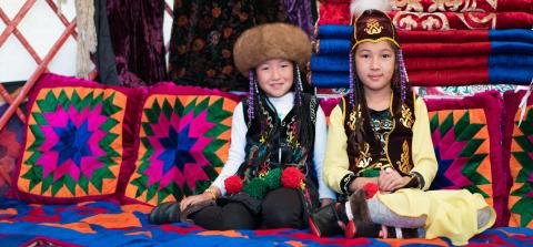 Girls sit in national costumes in Kyrgyzstan