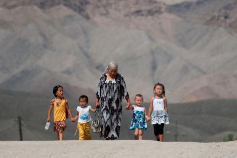 An old lady walks down the road with her grandchildren
