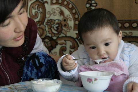 a child eats with his mother