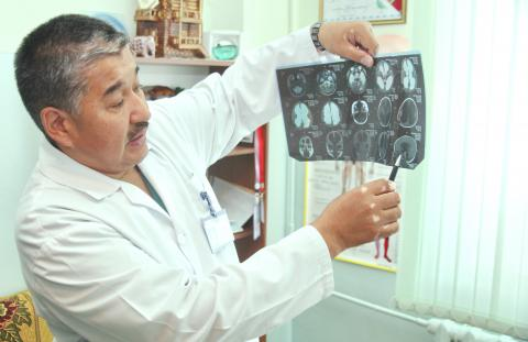 A male doctor in lab coat holds up a scan to the light