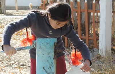A girl pumps water into container