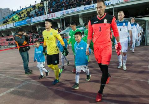 Footballers walk onto field holding hands with children in UNICEF sweatshirts
