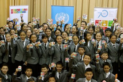 A group of children in matching grey uniforms hold up mugs with SDGs printed on them