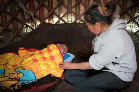 A mother watches her baby sleeping under a yellow blanket