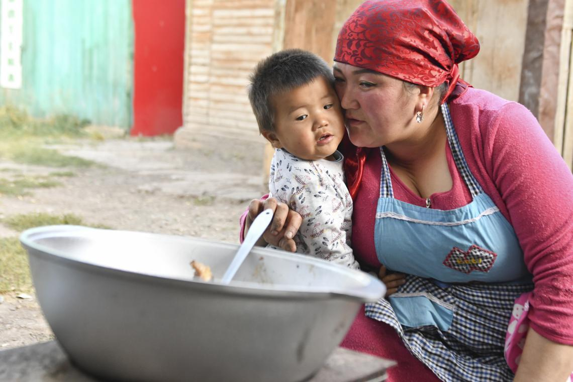 Dr. Pakirova cooking a meal with one of her children