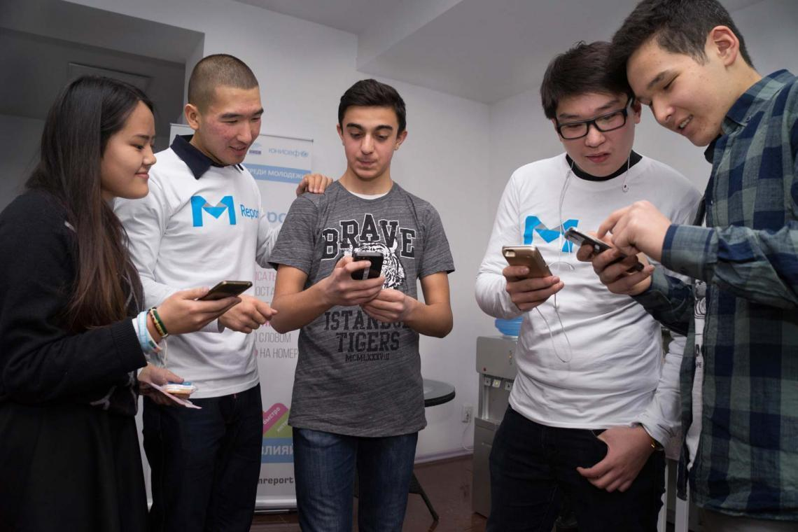 Babinur (20) (left), UNICEF consultant Isabek Asanbaev, Denis (15), Suleiman (16) and Ulugbek (15) all have great expectations for M-Report in Kyrgyzstan.