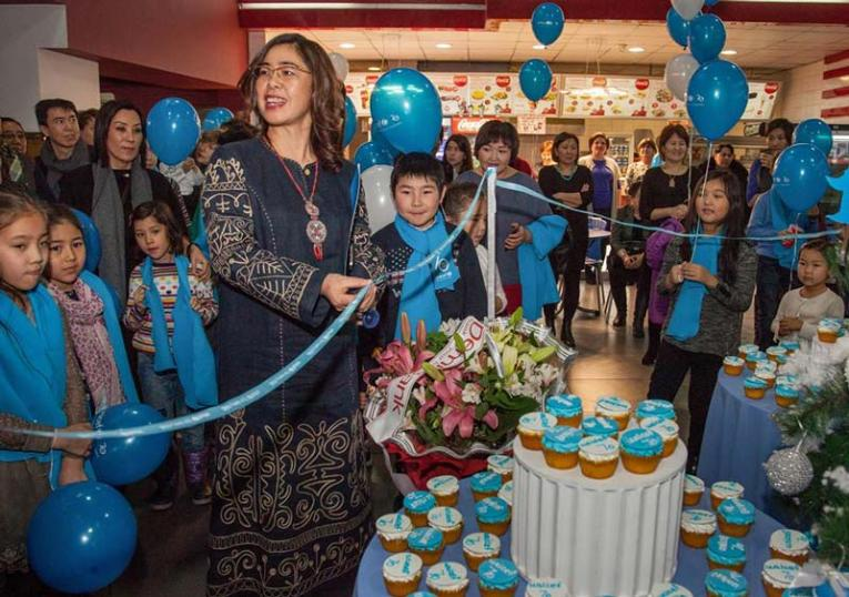 A woman looks off camera standing amongst children in blue scarfs; UNICEF-themed cupcakes and balloons decorate the room