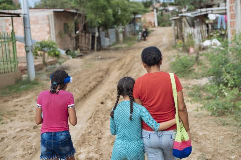 On 23 April 2019 in Cucuta, Colombia, Acnayeli Campos (center), 9, wants to be a photo journalist when she grows up. She walks home with her mother and her sister, Andaili.
