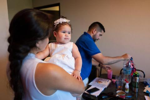 Milagos lifts her 14-months daughter Paula, while her husband serves water in the family's apartment in Paraguay