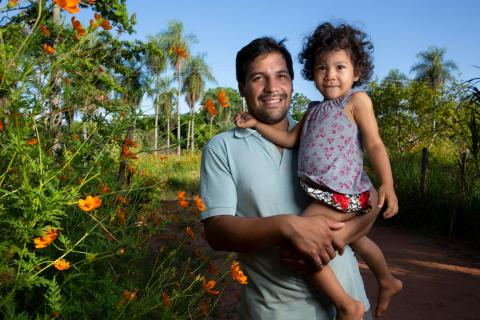 Rafael Alfonso Araujo, 27, holds his daughter Selva, 2, outside of their home in Paraguay
