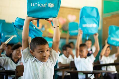 Manuel Altamiranda, 8-year-old, with his classmates raising in the air their UNICEF education kit, Maracaibo, September 2019.