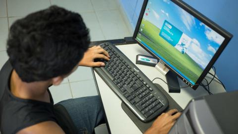 Jesus, 15, sits at a computer at the UNICEF-supported Fundacion National Para Desarrollo de Honduras