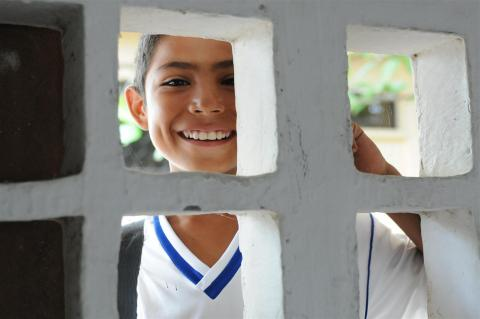 César, 12, a sixth-grade student, smiles as he peers through a cement block window of a classroom in Colombia
