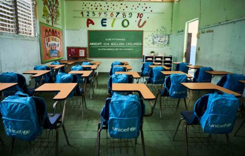 Empty classroom with backpacks on the chairs' back.
