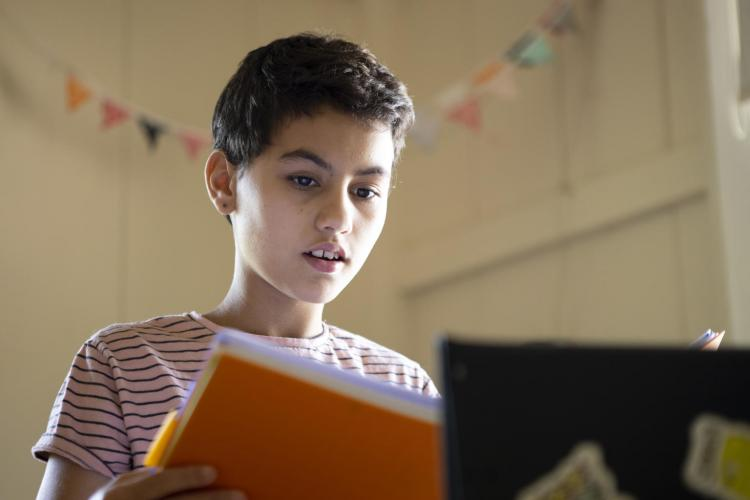 Mila, 11, reads out loud her latest writing production to her teacher and classmates during a live online class offered on the Zoom platform at home in Panama