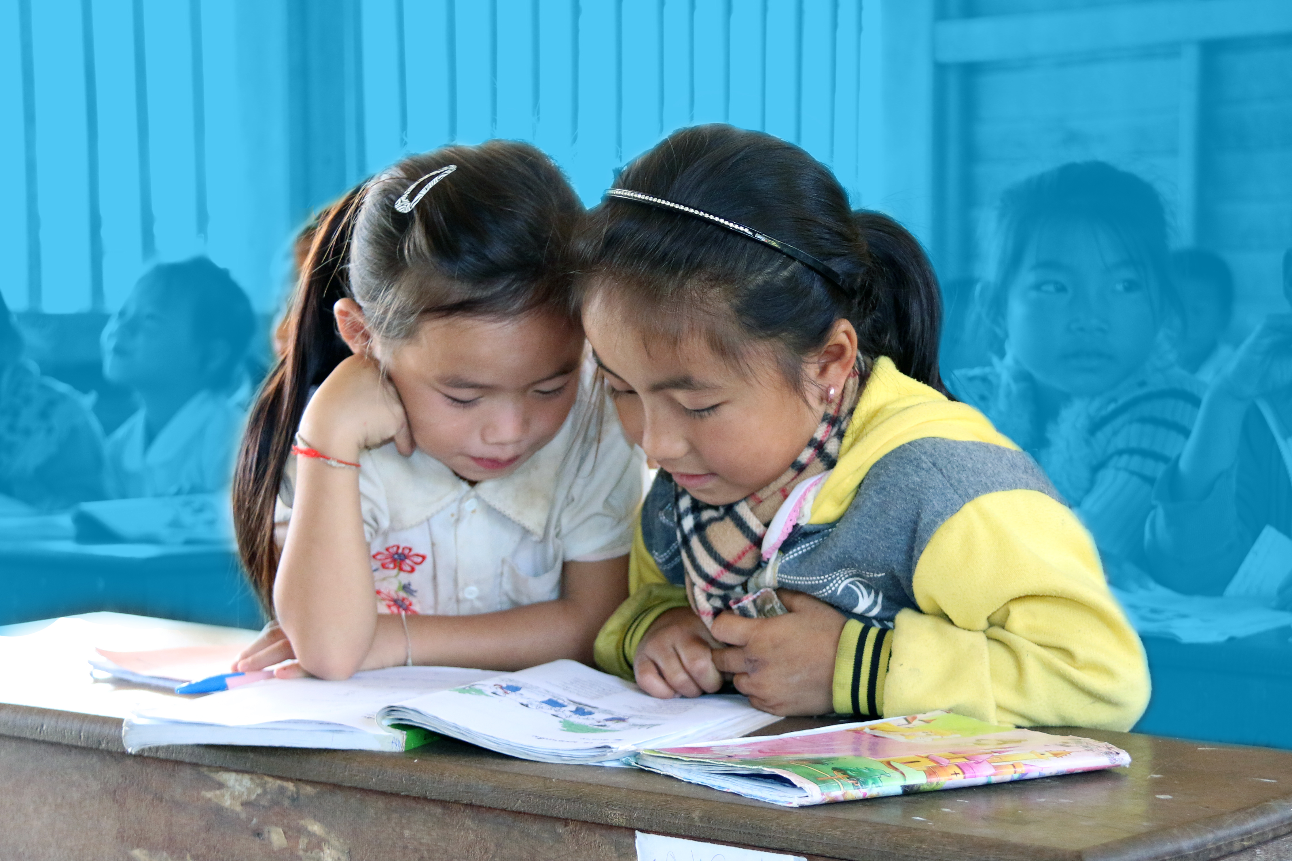 Two students are reading book in the class