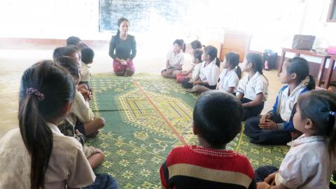 20 children (14 girls) sit in a circle on the mat paying attention to the pre-primary teacher who is giving instructions for a learning activity