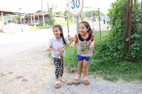 Two little girls playing on shoes made of coconut shells