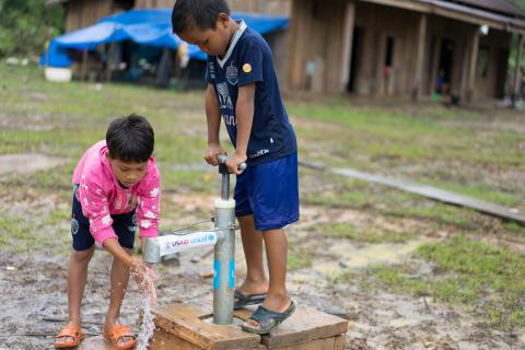 Two boys use a UNICEF- and USAID-supported tap in Ban Bok camp, Attapeu, Lao PDR.