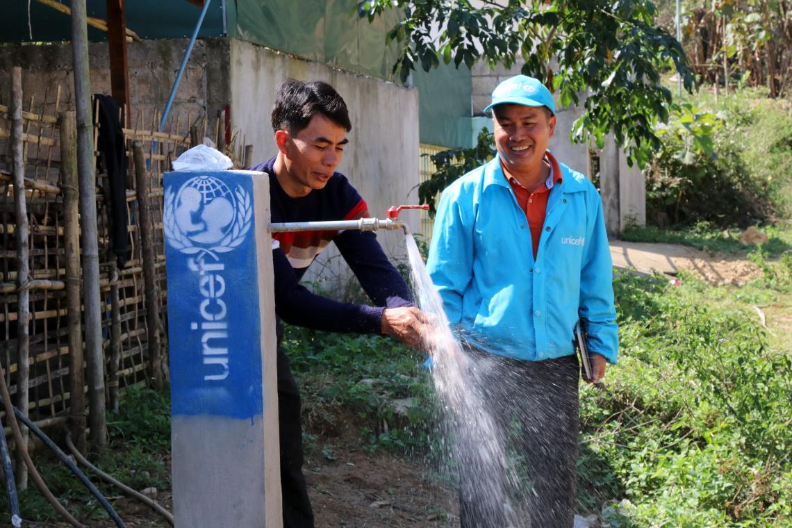 Khamsao Savixay, WASH Mai district technical staff proudly showing the new water tank in his village, that has been supported by UNICEF to Bandith (right) in SopHoon village, Mai district, Phongsaly province, 2018