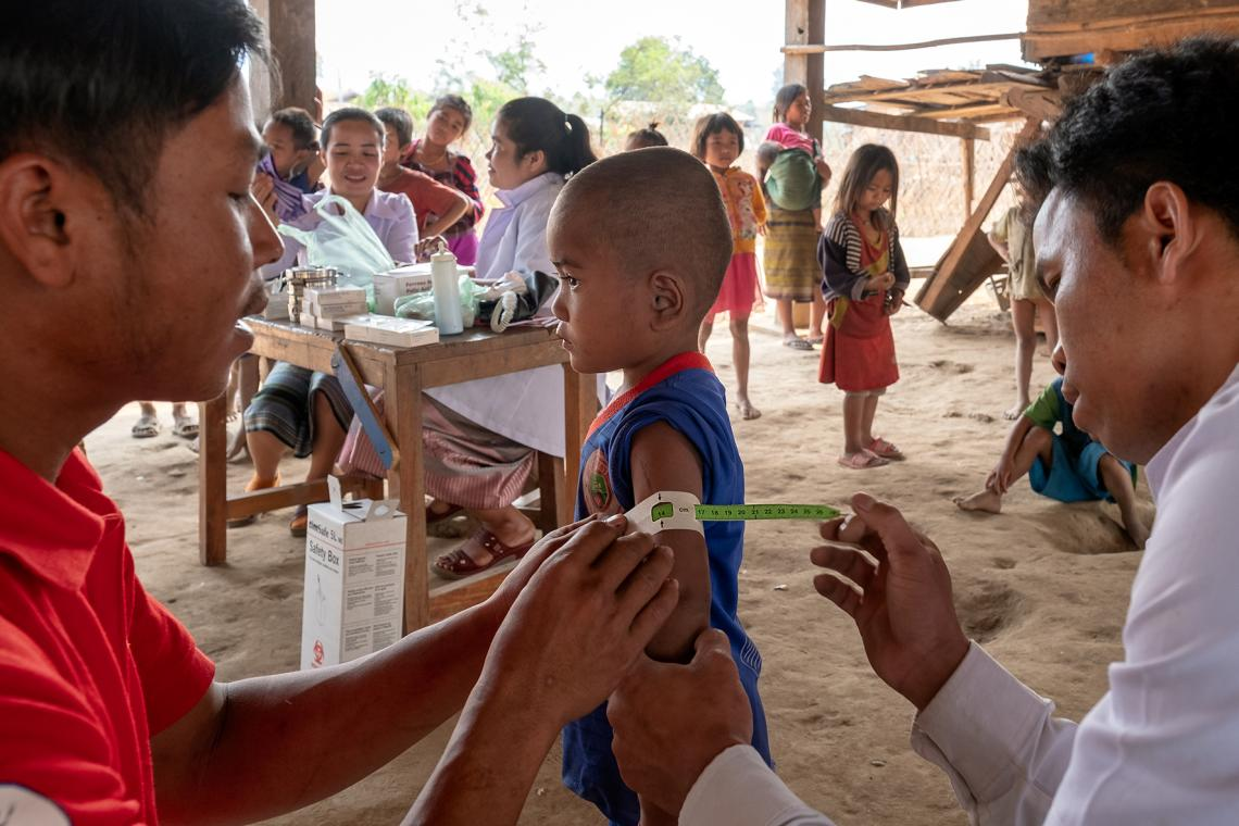 Phetsamay and a health volunteer screen a child for acute malnutrition.