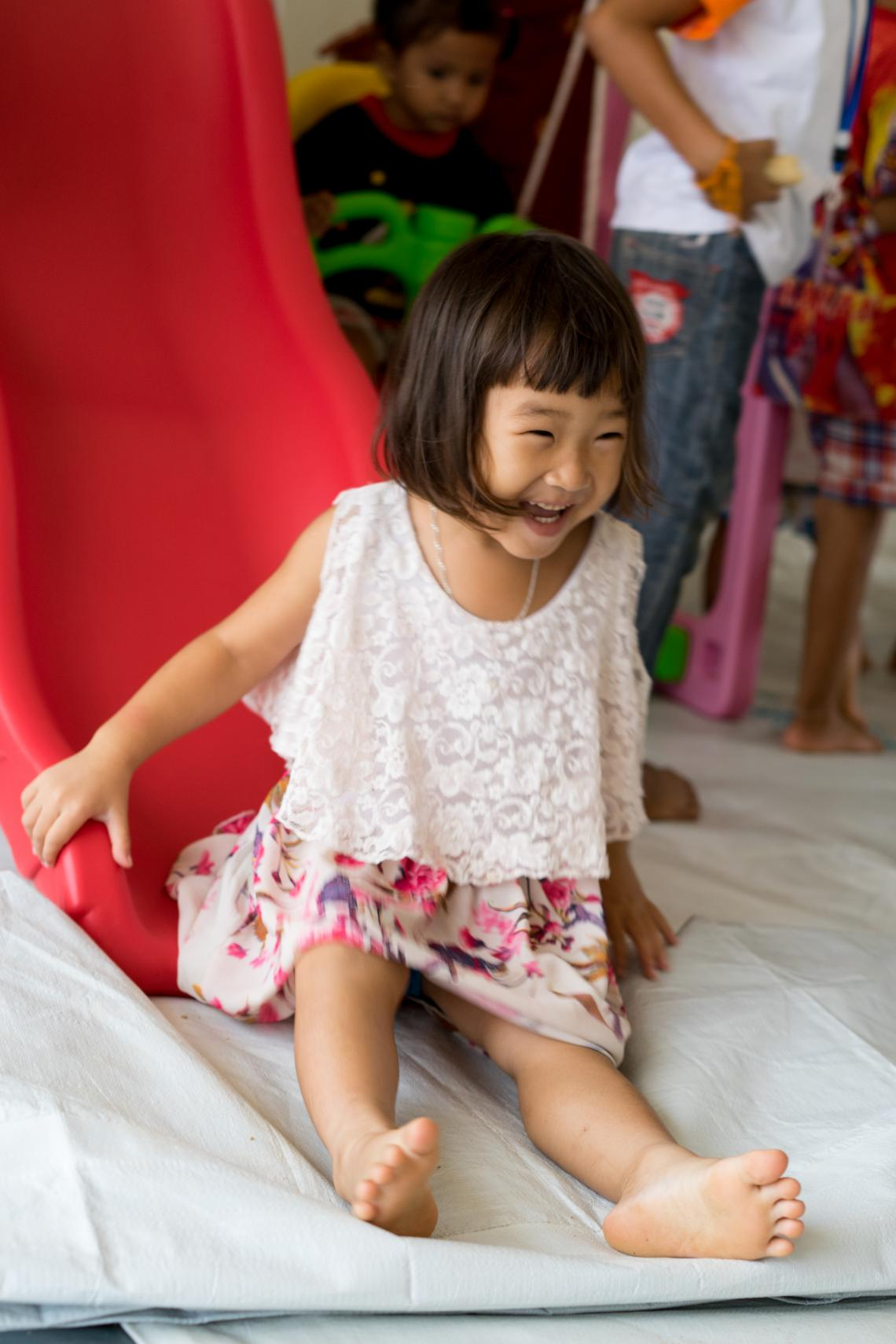 A girl laughs while on a slide in a UNICEF-supported Child Friendly Space in Sanamxai Camp, Attapeu, Lao PDR.