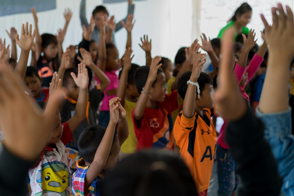 Children affected by recent floods raise their hands during a fun activity in a Child Friendly Space in Ban Bok camp, Attapeu, Lao PDR.