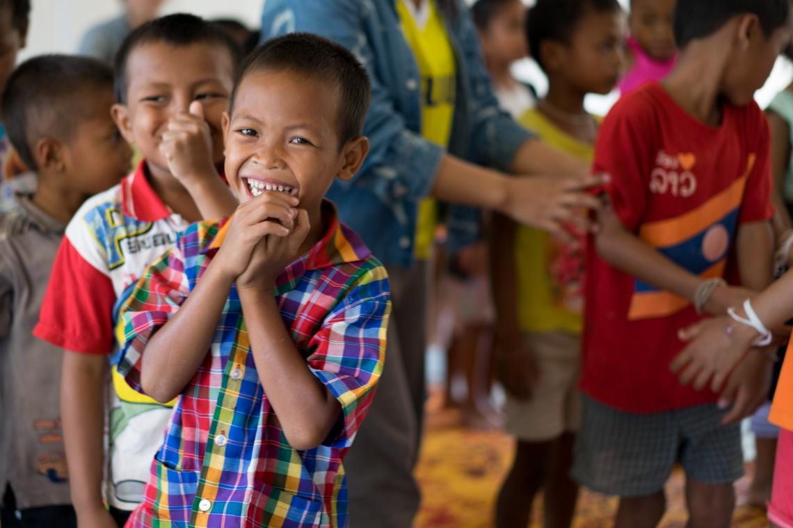 A boy laughs while taking part in activities in a UNICEF-supported Child Friendly Space