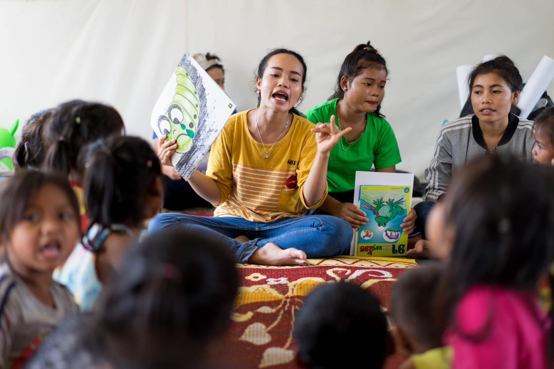 Volunteer teacher Maliathone takes flood-affected children through a story telling activity in a UNICEF-supported Child Friendly Space, Ban Bok camp, Attapeu, Lao PDR.