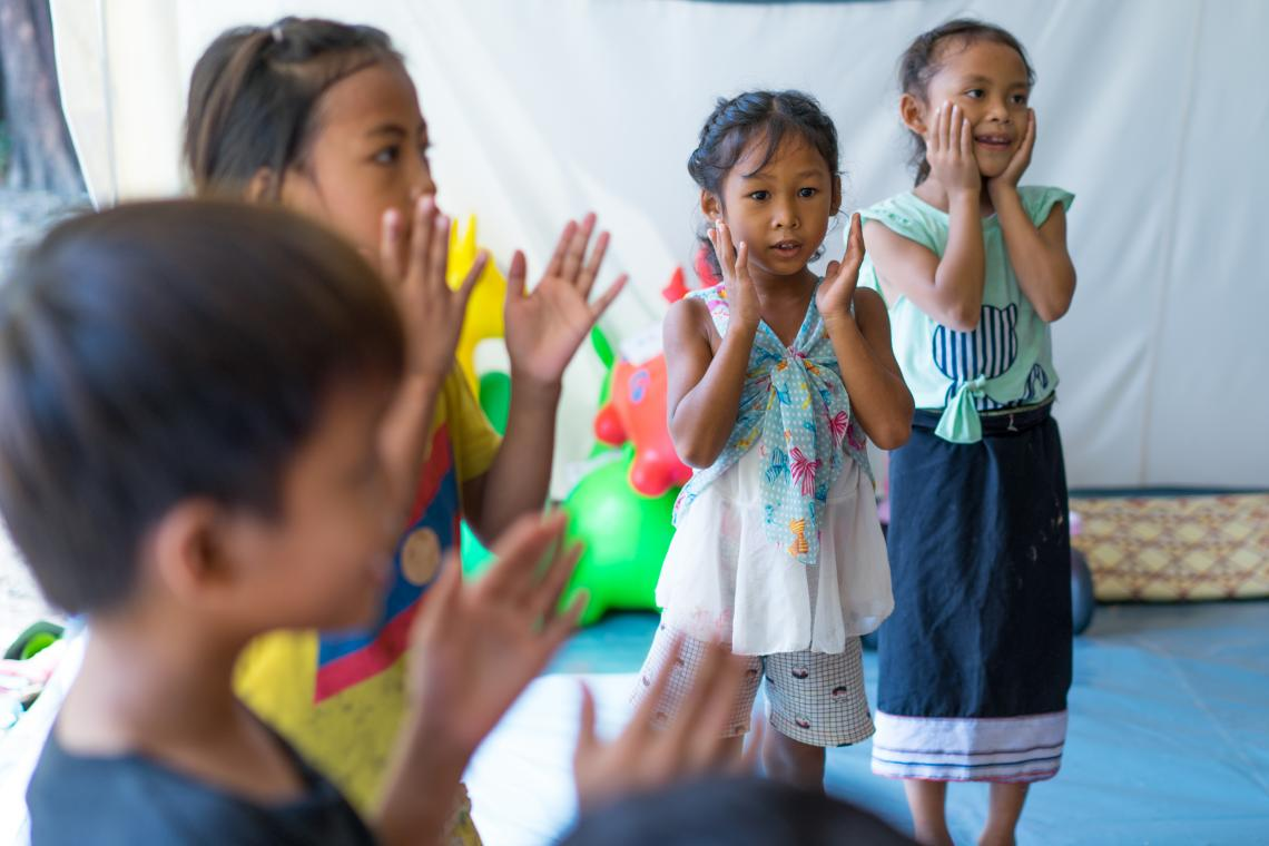Laura, 6, second from right, takes part in 'the mango game' in a UNICEF-supported child friendly space in Ban Bok camp, Attapeu, Lao PDR.