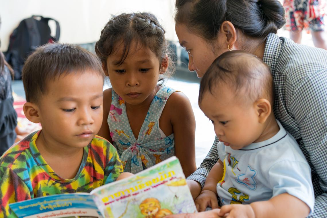 Laura, 6, centre, take part in a reading activity in a UNICEF-supported Child Friendly Space in Ban Bok camp, Attapeu, Lao PDR.