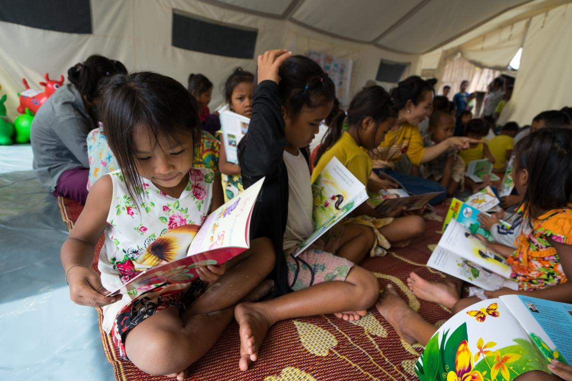 A young girl reads with other flood-affected children in a UNICEF-supported Child Friendly Space