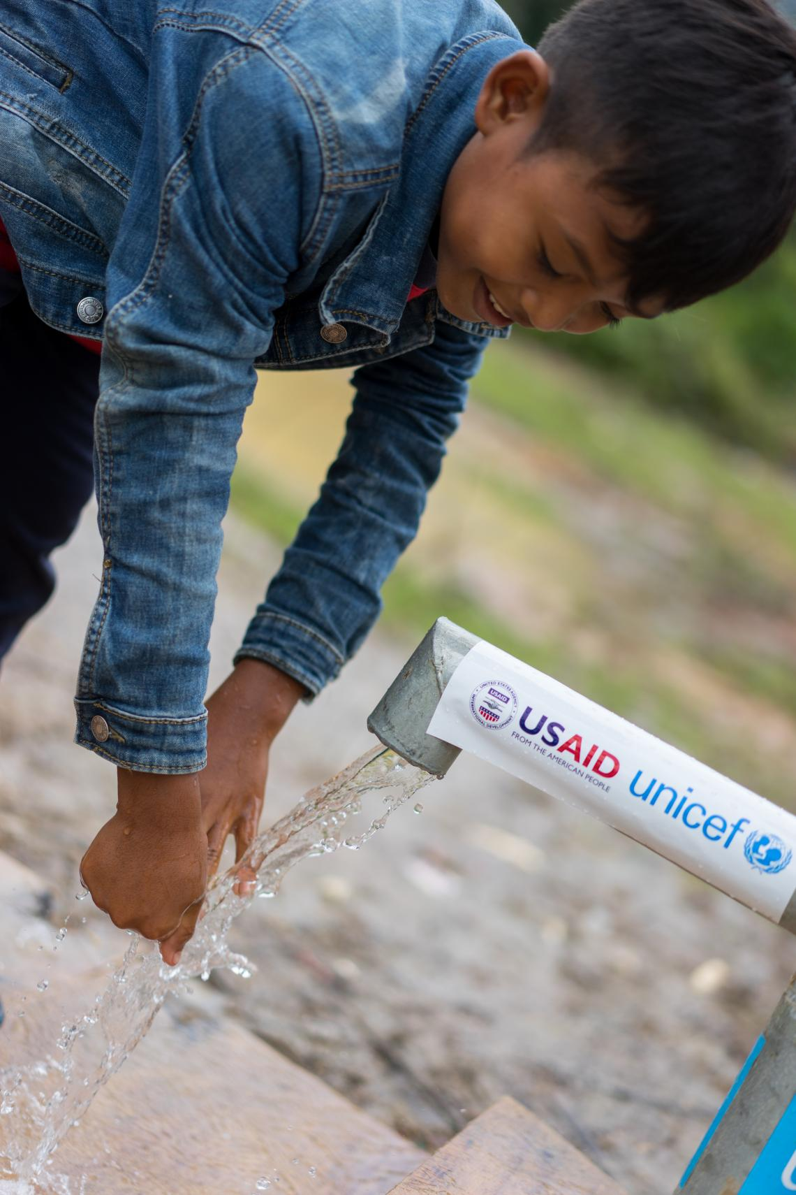 Khao Yai, 12, uses a UNICEF- and USAID-supported tap in Ban Bok camp, Attapeu, Lao PDR.