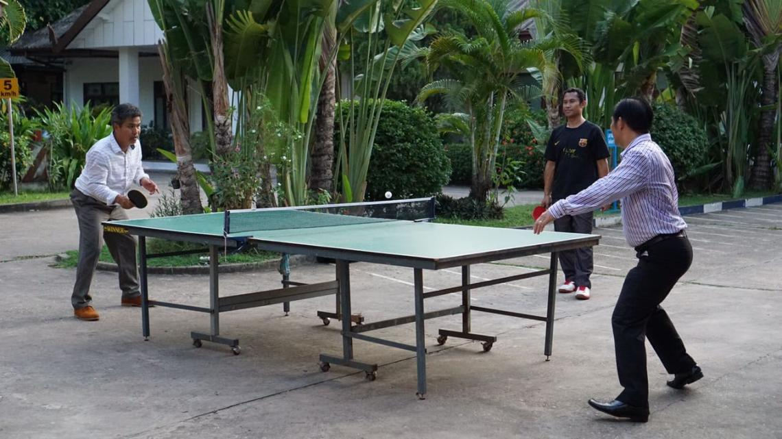 Bandith (left) playing ping pong with colleagues after a hard day's work