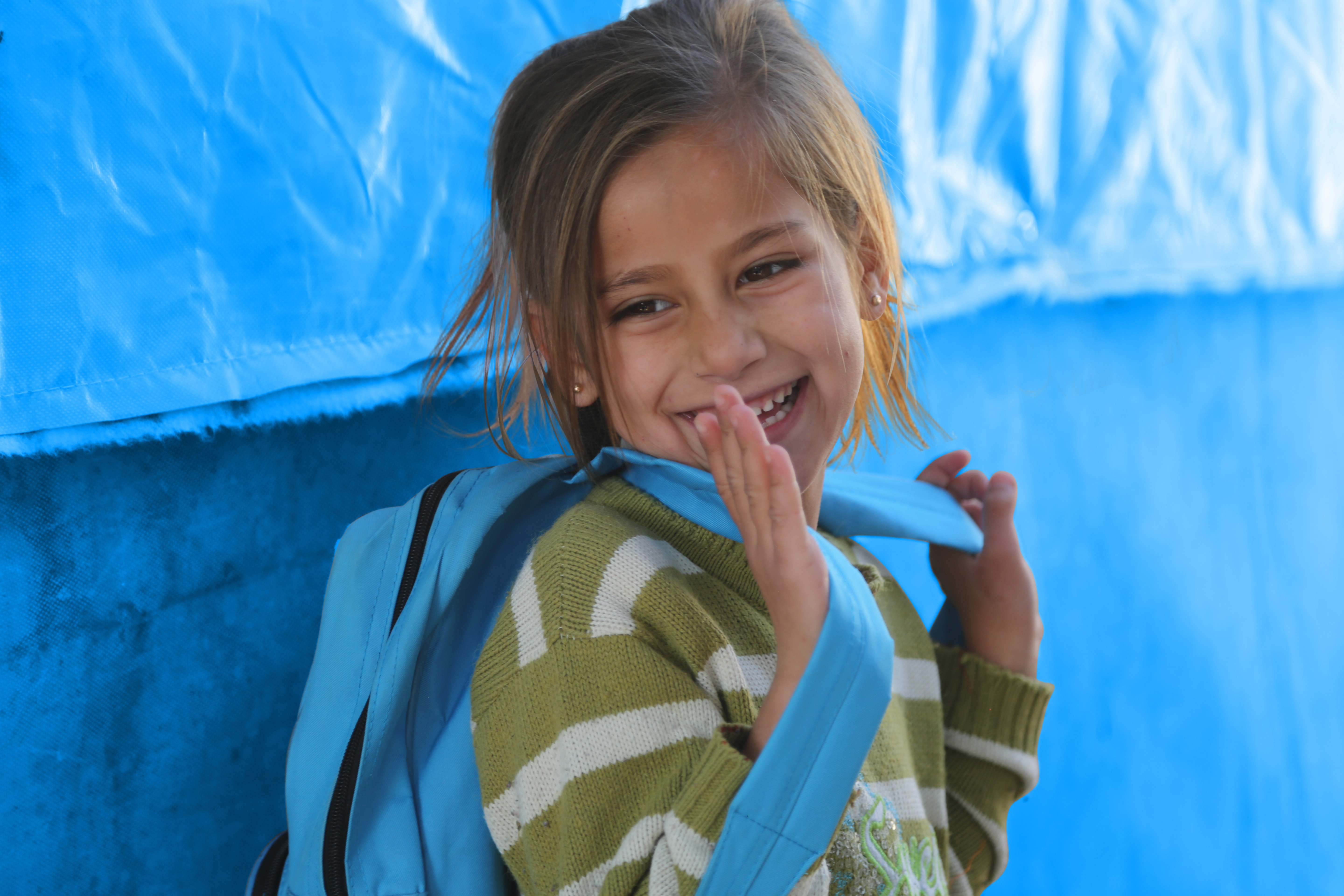 A girl by her family tent in Nizip 1 refugee camp, Gaziantep, southern Turkey
