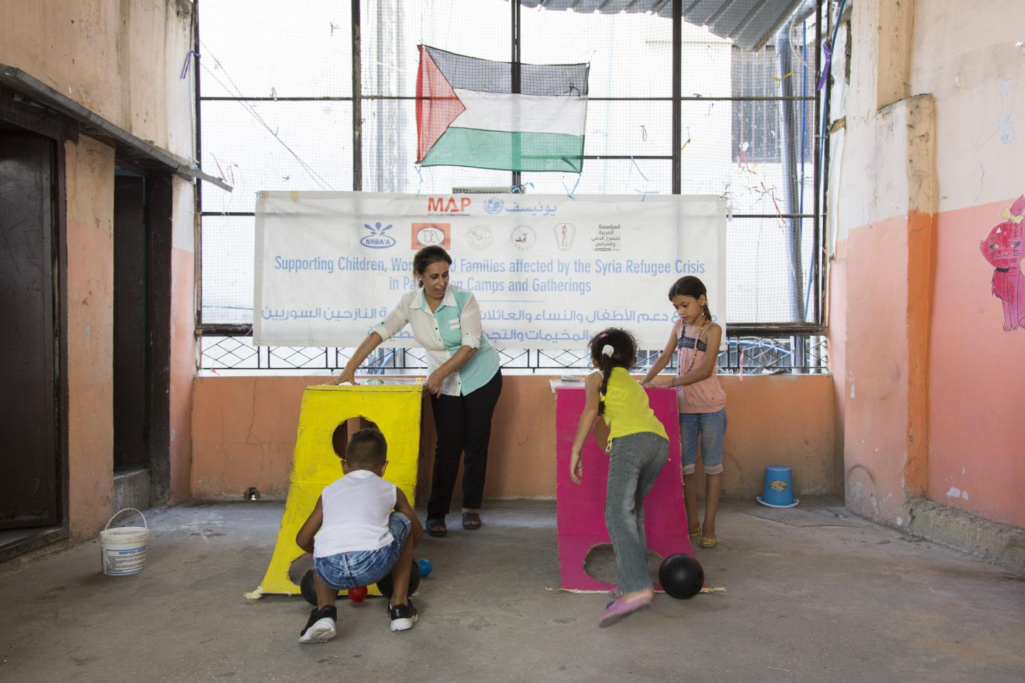 Palestinian refugee children throw the balls into holes during a basketball activity at the Tadamon center at the Ein el Helweh Palestinian refugee camp, in Saida, south of Lebanon.