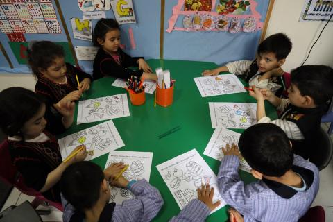 Children sitting in class participating in a coloring activity.