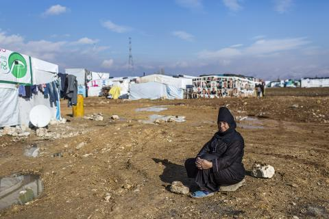 Syrian woman sitting in front of the camp.