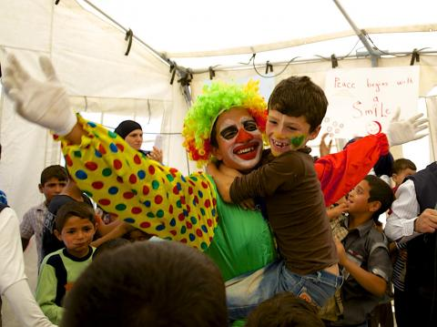Clown at a camp playing with children.