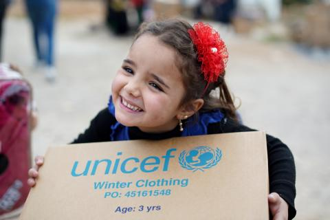 Little girl smiling as she receives UNICEF supply box.