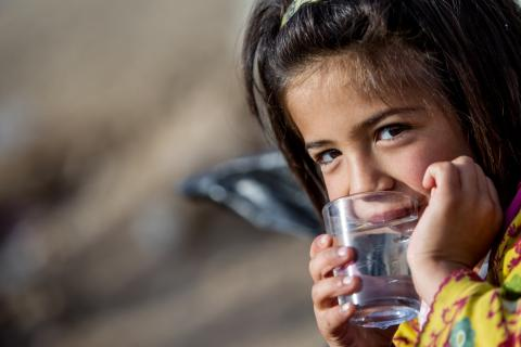 Young Syrian girl drinks water