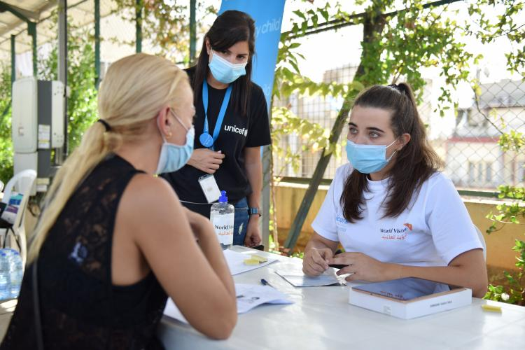 World vision volunteer next to UNICEF staffer during the onsite registration of the emergency cash grant