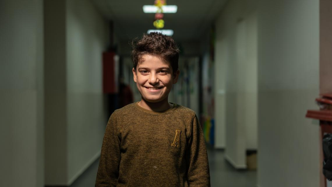 Hayan stands in a school hallways, with a big smile on his face