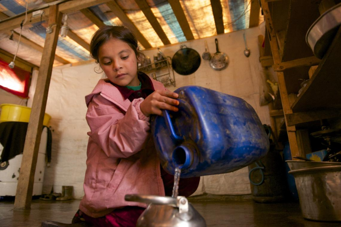 Girl pouring water into a kettle from a water tank.
