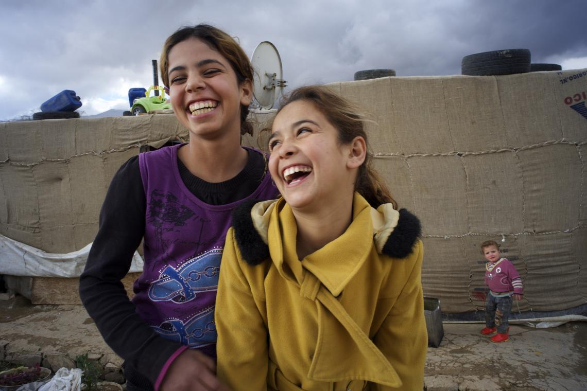 Two girls laughing in a field as their hope surges once again.