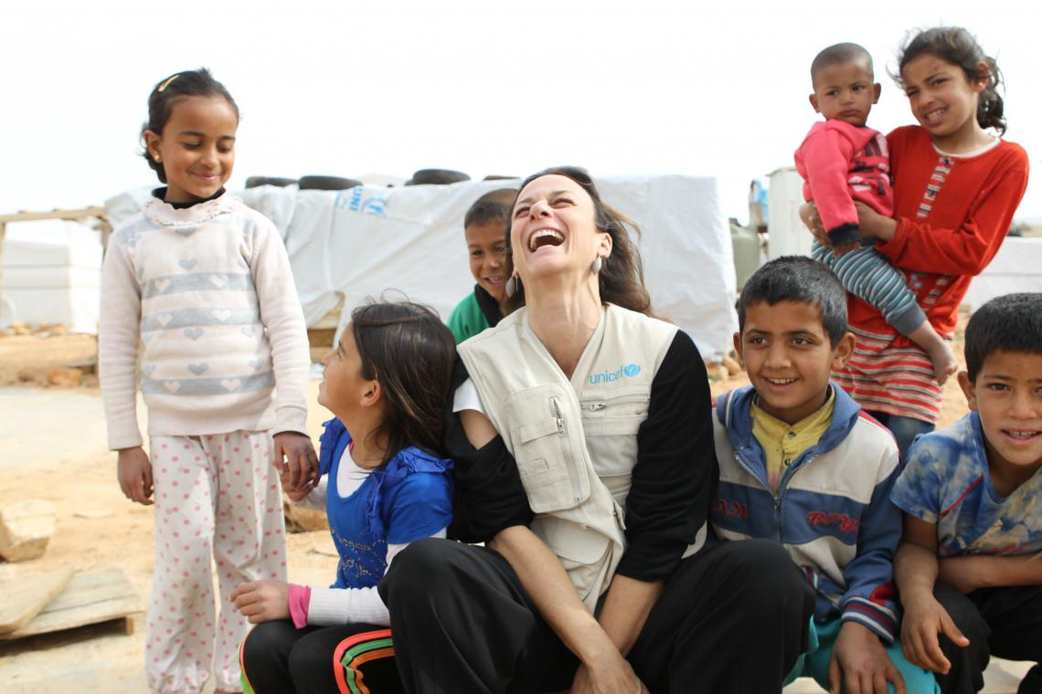 UNICEF Representative surrounded by Syrian refugees